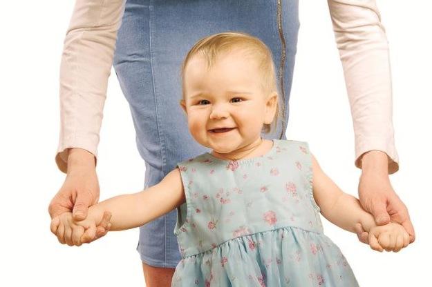Ucząc się chodzić dziecko może trzymać mamę za rękę