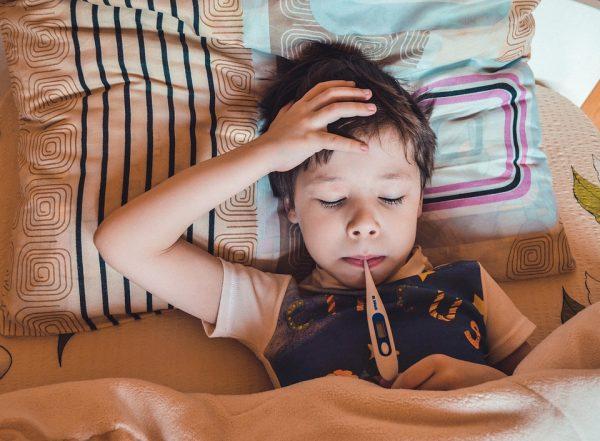 infekcja wirusowa - chłopiec z gorączką leży w łóżku