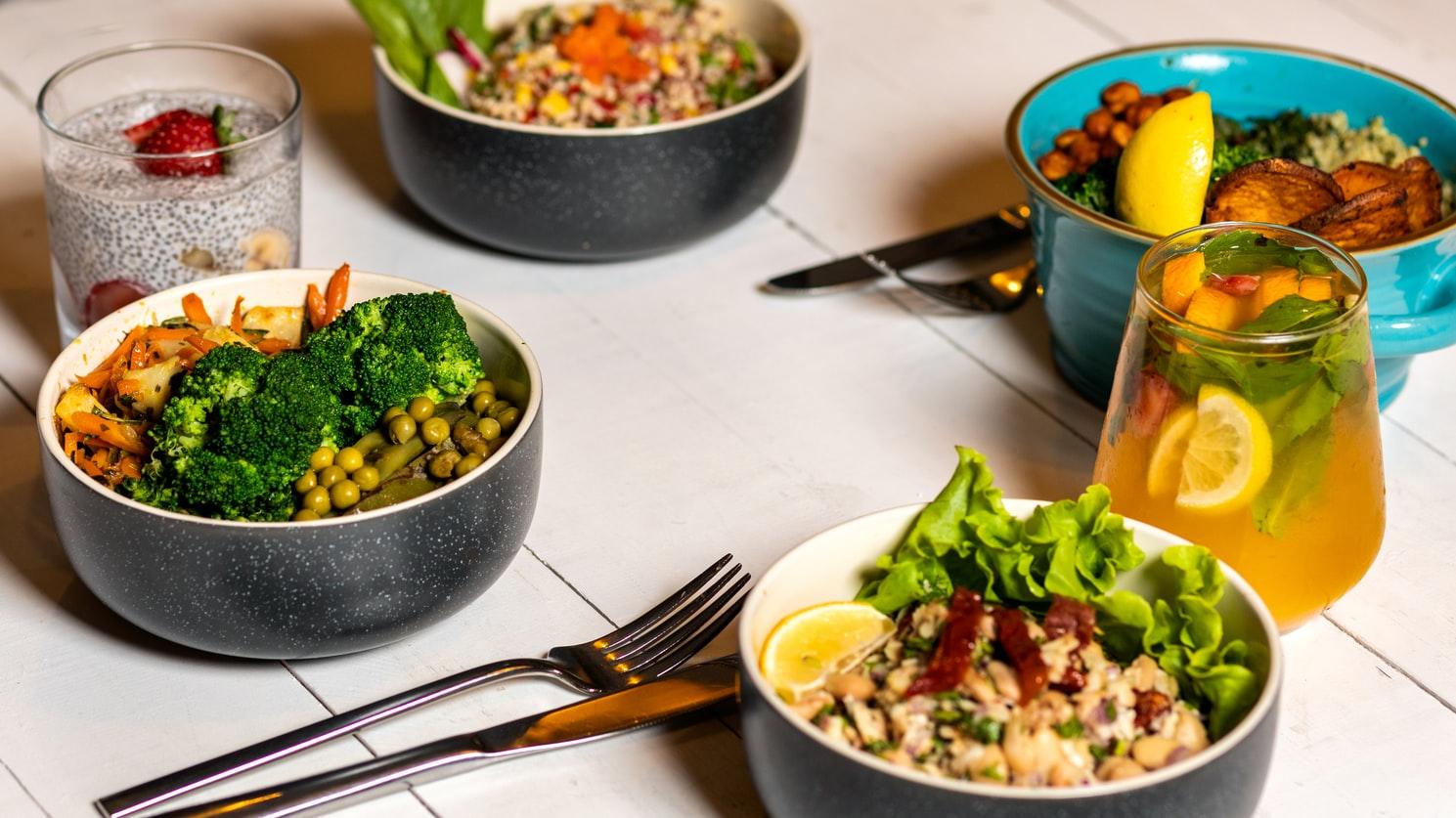 na stole stoją 4 miski ze zdrowym jedzeniem - brokuły, kasza, zielony groszek, sałata oraz sztućce i napoje