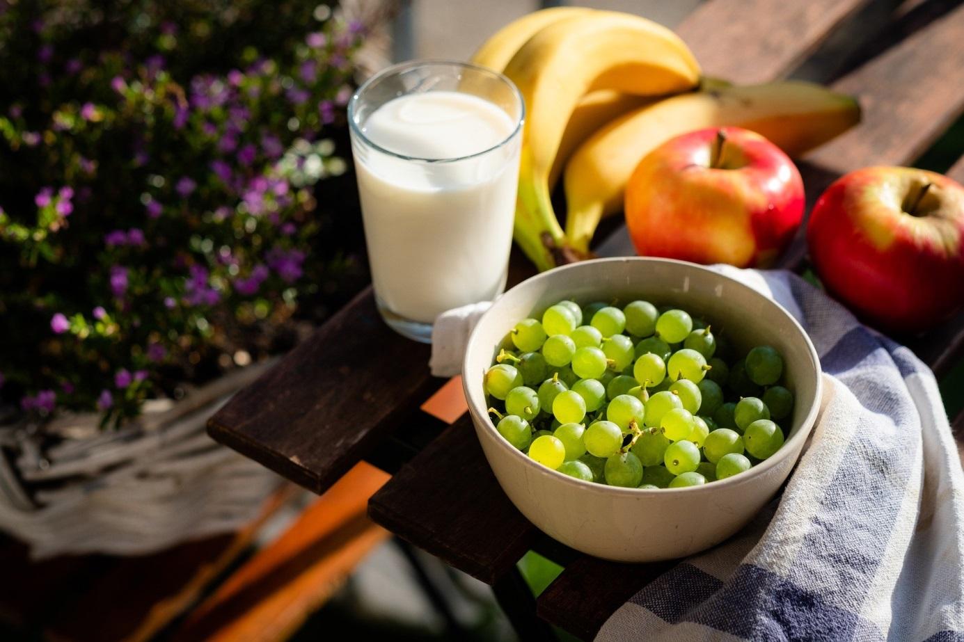 na stole stoją winogrona, jabłko i banany a obok szklanka mleka